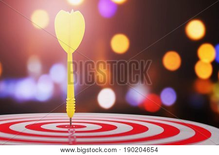 yellow arrow with over blurred background and target of dartboard or metaphor to target business concept