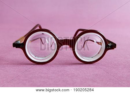 Old fashion design spectacles eyeglasses on pink violet paper background. Vintage style men fashion accessories for perfect vision. Macro view, shallow depth of field, soft focus