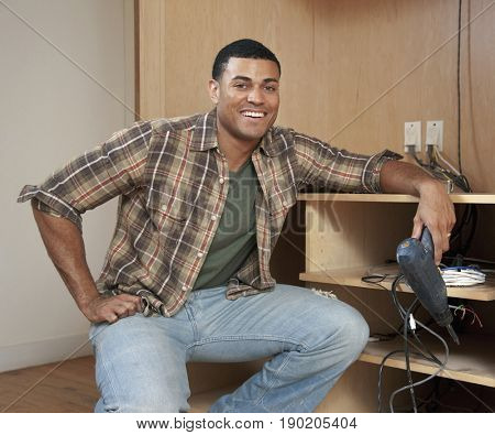 Mixed race man building cabinet