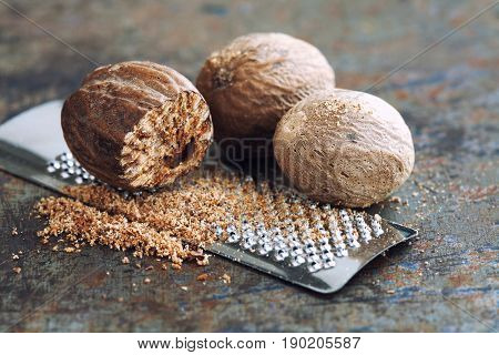 Making nutmeg powder process. Nuts silver grater. Kitchen still life photo. Shallow depth of field, aged brown rusty background. Selective focus photo