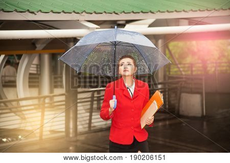 Thai pretty woman in red office suit holding transparent umbrella and document walking on bridge crossing  landmark in Bangkok city ,Thailand.