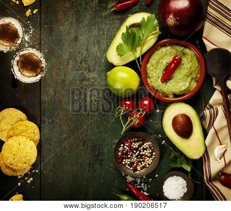 Bowl of Traditional latinamerican mexican sauce guacamole with fresh ingredients and tequila shots on dark rustic background. Top view