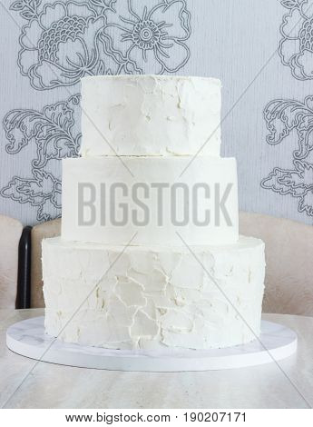 Naked white three-tiered cake without ornaments on the table
