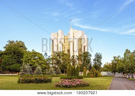 Tall white and golden presidency office of the president of moldova administration building, chisinau, blue sky at sunset, national flag