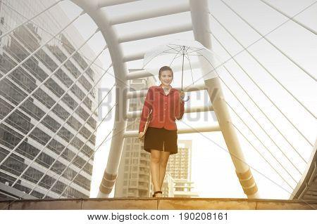Thai pretty woman in red office suit holding transparent umbrella walking on bridge crossing  landmark in Bangkok city ,Thailand.
