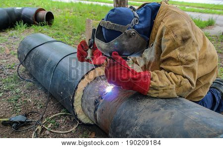 Metal Worker Welds Two Big Metal Pipes