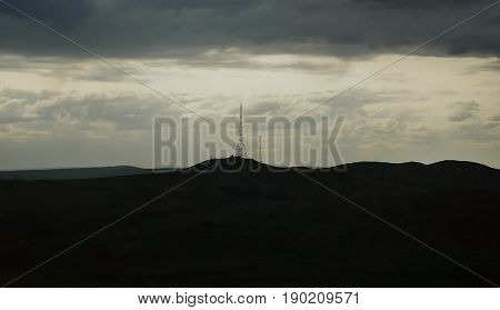 Silhouette of the hills and the TV tower. Silhouette of the TV tower. Silhouette of the hills. Natural background. Television tower. Horizon.