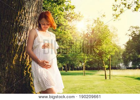 Beautiful pregnant woman in white dress on nature outdoors. Expectant mother holds hands on belly on natural background of green grass in park at summer. Pregnancy expectation new life concepts.