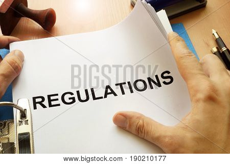 Documents with title Regulations on a table.