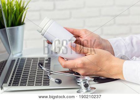 Female medicine doctor hands hold jar of pills