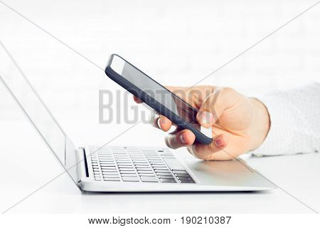 businessman is using laptop computer and smartphone