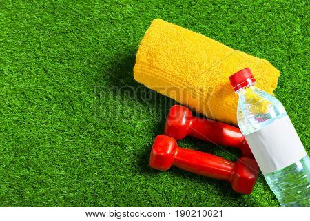 water bottle red dumbells and towel on green grass background