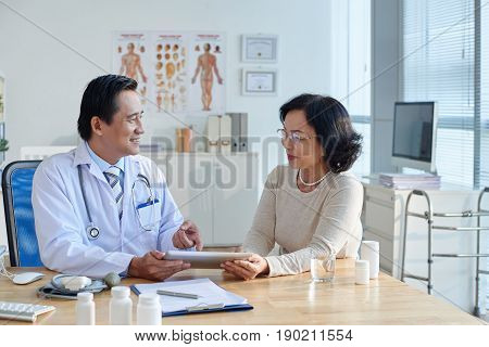 Profile view of friendly Asian cardiologist consulting his senior patient with help of digital tablet during check-up