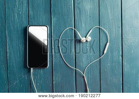 white earphones attached to smartphone on wooden background