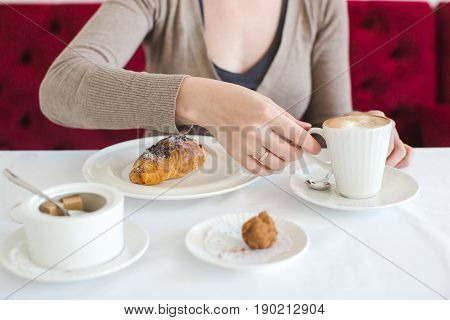 Woman having breakfast with a cup of cappuccino coffee next to a croissant lying, close-up of a white tablecloth, delicious coffee with croissant