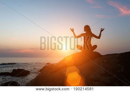 Yoga meditation silhouette. Fitness woman on the ocean during amazing sunset. Healthy lifestyle.