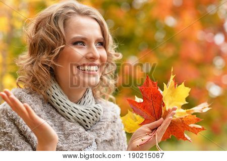 Beautiful young woman resting in autumnal park