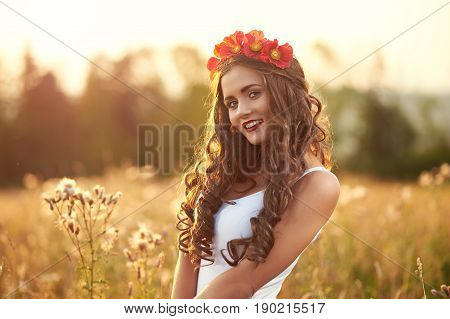 Young, beautiful, attractive model in swimsuit, posing in a field of flowers on the background of sunset, hairstyle, makeup, red corolla with flowers, model is looking at the camera, portrait.
