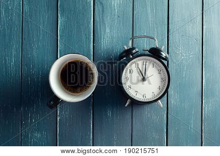 Still life with alarm clock and coffee cup on wood table