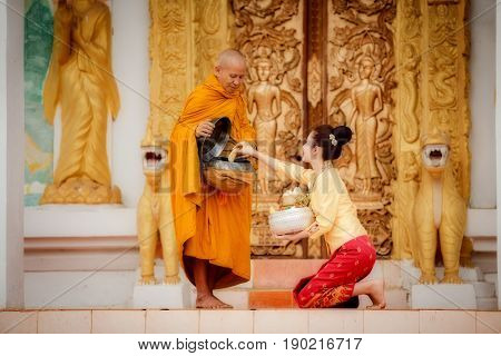 Beautuful Laos woman To give merit to monks of Buddhism. This lifestlye of asian people Thai Laos Myanmar and Cambodia in Southeast asia.