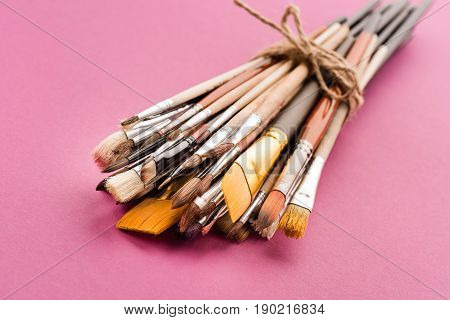 Close-up View Of Tied Various Paintbrushes Collection On Pink