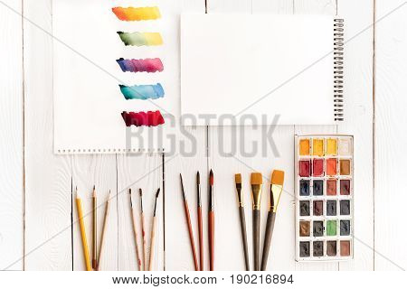 Top View Of Set Of Paints, Different Brushes, Blank Notebook And Colorful Brushstrokes On Paper