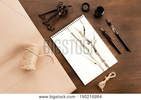 Top View Of Bamboo Drawing In Album, Brush, Fountain Pen And Vintage Keys On Table