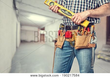 man with toolsbelt holding spirit level