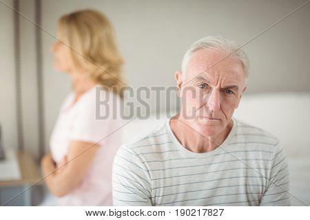 Worried senior man sitting on bed in bedroom