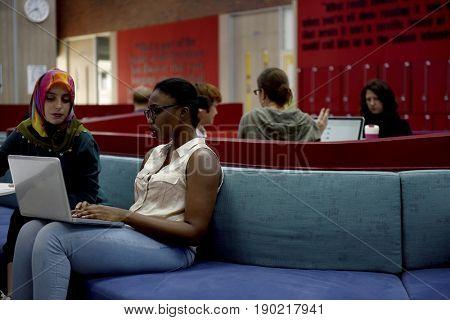 Diverse people sitting using laptop