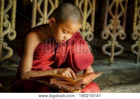 BURMA Little monk or Novice monk are reading the book in the temple of Buddhism Religion in Mandalay Myanmar.