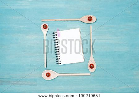Top View Of Wooden Spoons With Cherry Tomatoes And Blank Open Cookbook On Wooden Table