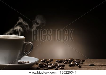 cup of steaming coffee on wooden table with roasted coffee beans.