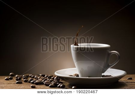 cup of coffee with coffee drop and coffee beans on wooden table.