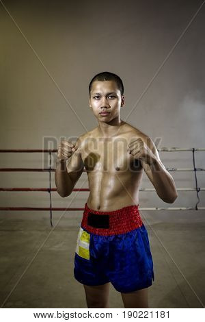 Portrait man Professional Muay Thai a strong ready for the fight in the fight of Muay Thai. This is a Martial art of Thailand and the world. Muay Thai boxer International extreme sport.