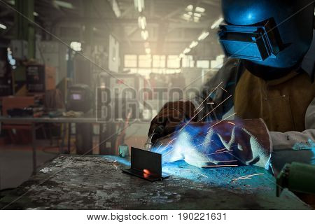 Masked worker Welding steel with gas in the factory during the operation by wearing a safety uniform for gas welding.