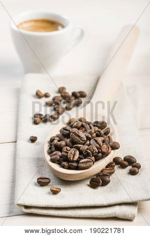 bunch of coffee beans on wooden spoon with cup of coffee on wooden table.