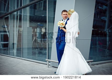 Groom In Blue Suit Leans To A Steel Building While Stading With A Bride
