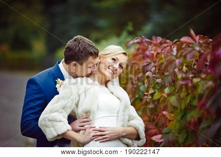 Fiance Kisses Bride's Neck Standing Behind The Red Bushes