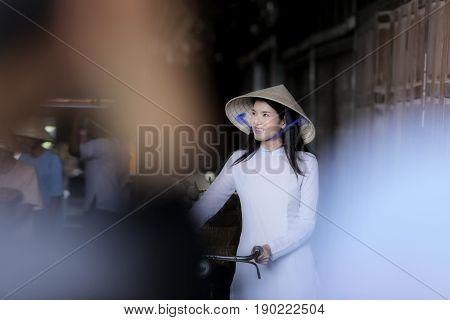 Beautiful women wearing Ao Dai dress traditional Vietnamese Cycling smile happily