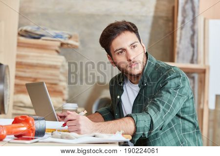 Craftsman with computer thinking during coffee break