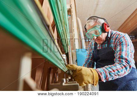 Senior citizen as carpenter controling vertical saw
