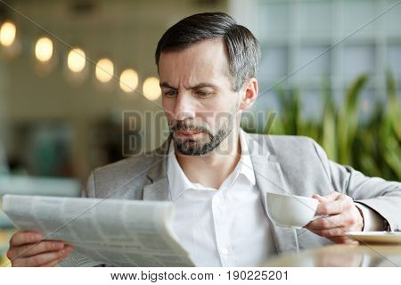 Serious and busy man with cup of tea reading morning news in cafe