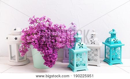 Lilac flowers in box and brigh lanterns on white wooden background against grey wall. Selective focus. Place for text. Toned image.