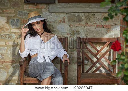 Beautiful woman on the terrace of an Italian country garden