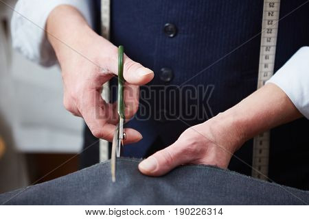 Closeup of skilled tailor working in atelier: hands cutting fabric with scissors while making clothes