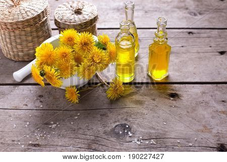 Fresh yellow flowers tussilago in mortar on wooden background. Wellness setting. Selective focus. Place for text.