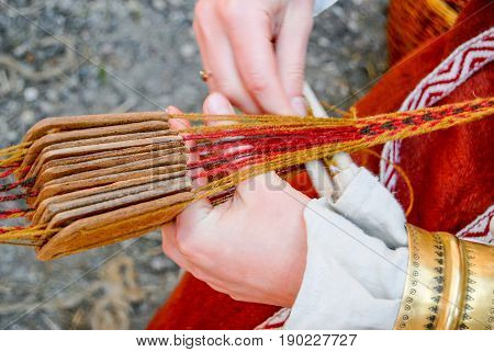 Woman hands weaving a traditional ethnic belt