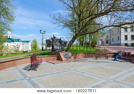 VITEBSK BELARUS - MAY 15 2017: Unknown girl is resting in park named after Pushkin near monument to Alexander Sergeevich Pushkin Vitebsk Belarus