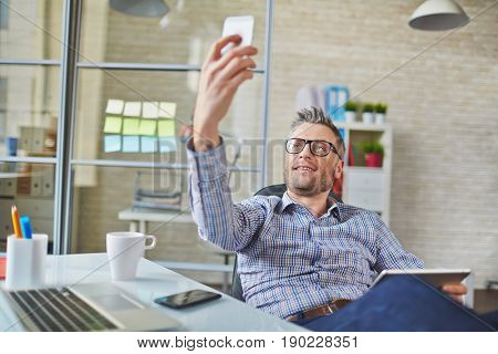Relaxed middle-aged businessman with tablet sitting on office chair and posing for self-portrait on smartphone